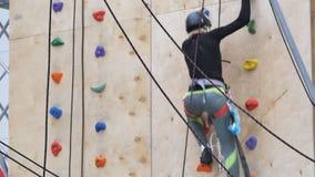 Muchacha que practica en la pared para la escalada almacen de metraje de vídeo