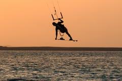 Muchacha que practica surf de la cometa en traje de baño con la cometa en cielo a bordo en movimiento de salto del truco del esti imagen de archivo libre de regalías