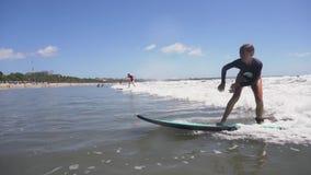 Muchacha que practica surf en el océano almacen de metraje de vídeo