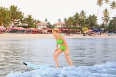 Muchacha que practica surf en el océano Imagen de archivo libre de regalías