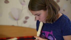Muchacha que practica tocando la flauta en casa almacen de video