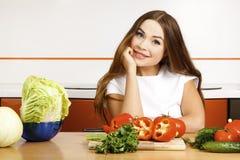 Muchacha que prepara la ensalada en la cocina. Imagen de archivo