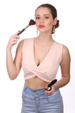 Muchacha que presenta con el cepillo del maquillaje Cierre para arriba Fondo blanco Foto de archivo libre de regalías