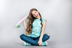 Muchacha que presenta con el monopatín que se sienta en el estudio Alegría, sonrisa, emociones positivas Fotos de archivo libres de regalías