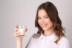 Muchacha que presenta con el vidrio de leche Cierre para arriba Fondo blanco Imagen de archivo libre de regalías