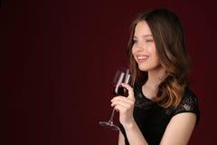 Muchacha que presenta con la copa Cierre para arriba Fondo rojo oscuro Imagen de archivo