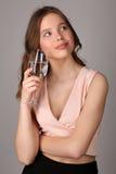 Muchacha que presenta con la copa de vino de agua Cierre para arriba Fondo gris Imagen de archivo libre de regalías