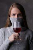 Muchacha que presenta con la copa y la cara cubierta Cierre para arriba Fondo gris Imagen de archivo libre de regalías