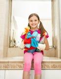 Muchacha que presenta con las botellas y los trapos de la despedregadora que presentan en el cuarto de baño Imagen de archivo libre de regalías