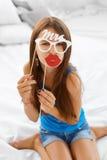 Muchacha que presenta con los apoyos de los labios y de las lentes Imagenes de archivo