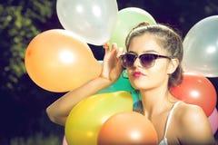 Muchacha que presenta con los globos en naturaleza Fotos de archivo