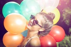 Muchacha que presenta con los globos en naturaleza Fotografía de archivo libre de regalías