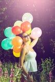 Muchacha que presenta con los globos en naturaleza Imagen de archivo