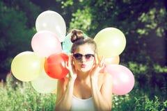Muchacha que presenta con los globos en naturaleza Imagenes de archivo