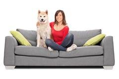 Muchacha que presenta con su perro asentado en un sofá foto de archivo