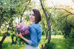 Muchacha que presenta con un ramo de lila Imágenes de archivo libres de regalías