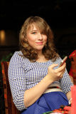Muchacha que presenta con un smartphone Imágenes de archivo libres de regalías