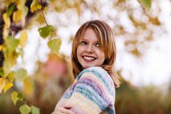Muchacha que presenta debajo de follaje en la estación del otoño Fotos de archivo