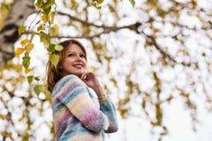 Muchacha que presenta debajo de follaje en la estación del otoño Imagen de archivo