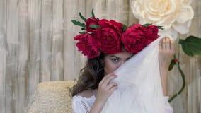 Muchacha que presenta delante de cámara la mujer joven en una guirnalda de las peonías del escarlata en su cabeza, pelo rizado la almacen de metraje de vídeo