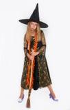 Muchacha que presenta en el vestido de la bruja, Halloween Imágenes de archivo libres de regalías