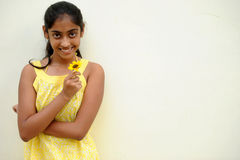 Muchacha que presenta en la pared amarilla con la flor Imágenes de archivo libres de regalías
