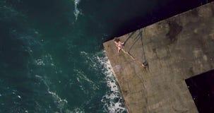 Muchacha que presenta en orilla del mar almacen de video