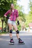 Muchacha que presenta en parque con sus cuchillas encendido Foto de archivo libre de regalías