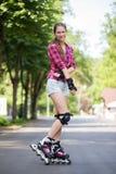 Muchacha que presenta en parque con sus cuchillas encendido Foto de archivo