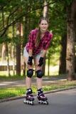 Muchacha que presenta en parque con sus cuchillas encendido Imagenes de archivo