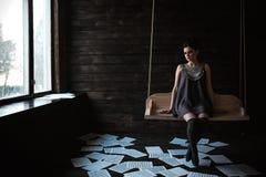 Muchacha que presenta en un cuarto oscuro Fotografía de archivo