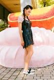 Muchacha que presenta en un parque en vidrios cerca de una melcocha y de una naranja grandes Fotos de archivo libres de regalías