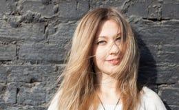 Muchacha que presenta en una pared de ladrillo negra El viento rizó su pelo Cierre para arriba outdoor Foto de archivo libre de regalías