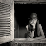 Muchacha que presenta en una ventana abierta Imagen de archivo libre de regalías