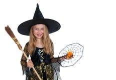 Muchacha que presenta en vestido de la bruja con la escoba y la araña Fotos de archivo
