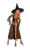 Muchacha que presenta en vestido de la bruja con la escoba y la araña Imagen de archivo