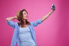 Muchacha que presenta para hacer un selfie vía cámara retra Fotos de archivo libres de regalías