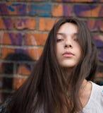 Muchacha que presenta sobre la pared de ladrillo. Foto de archivo
