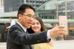 Muchacha que protagoniza en el smartphone mientras que el hombre que toma la foto del selfie Imagen de archivo