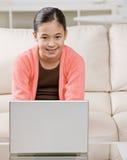 Muchacha que pulsa en la computadora portátil en sala de estar Fotos de archivo