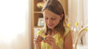 Muchacha que quita la envoltura del huevo de Pascua del chocolate almacen de video