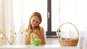 Muchacha que quita la envoltura del huevo de Pascua del chocolate almacen de metraje de vídeo