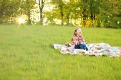 Muchacha que ríe en el edredón de la puesta del sol Imagenes de archivo