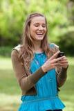 Muchacha que ríe mientras que lee un texto en su teléfono Foto de archivo libre de regalías
