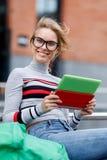 Muchacha que ríe mientras que se sienta en la calle con la tableta cerca del edificio Imágenes de archivo libres de regalías
