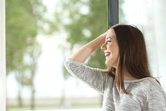 Muchacha que ríe y que mira a través de ventana Fotografía de archivo libre de regalías