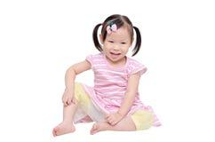 Muchacha que rasguña su pierna sobre blanco Imagen de archivo
