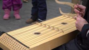 Muchacha que realiza m?sica con el instrumento tradicional de la secuencia en el precio en la calle metrajes