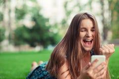 Muchacha que recibe un mensaje del SMS con buenas noticias en un teléfono móvil imagen de archivo
