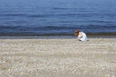 Muchacha que recoge cáscaras en la playa Imagen de archivo libre de regalías